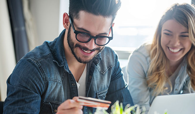 Smiling couple shopping online with credit card
