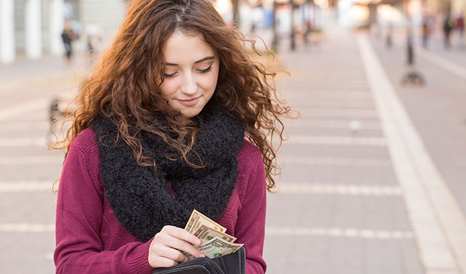 Woman putting cash in her wallet